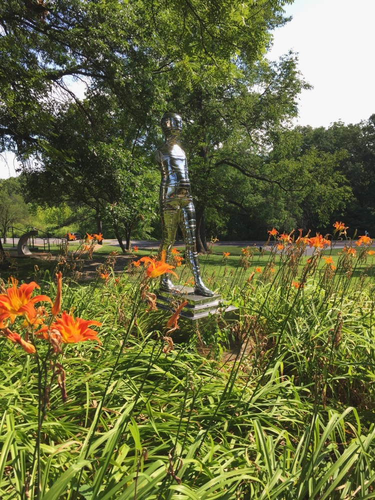 Silver sculpture surrounded by orange flowers