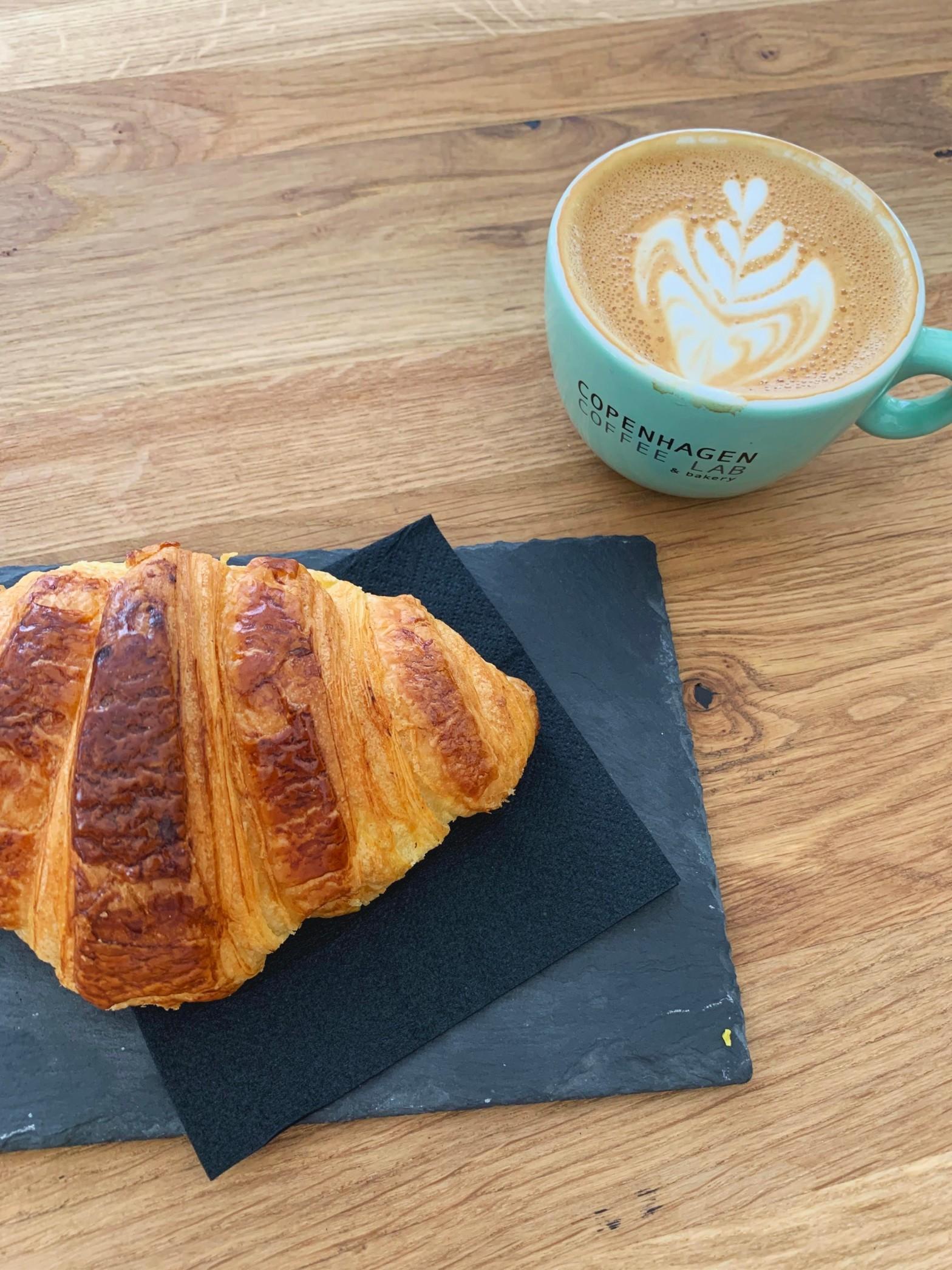 latte next to a croissant