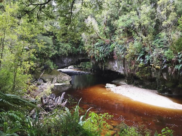 river running under a limestone arch
