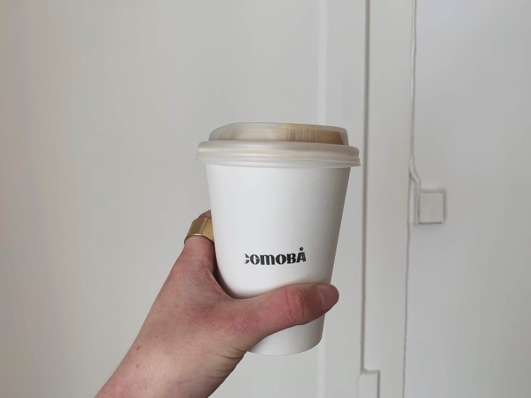 hand holding up a cup of coffee against a white wall