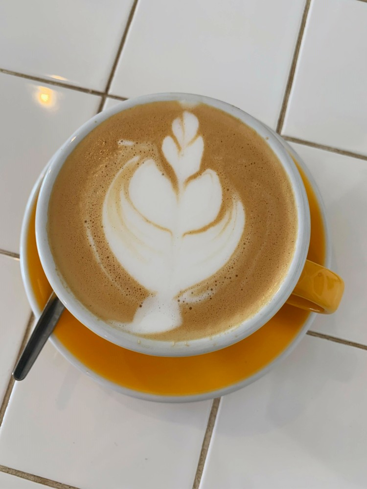 overhead view of a latte in a yellow cup