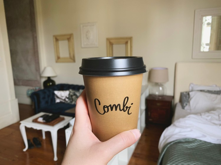hand holding up a cup of coffee