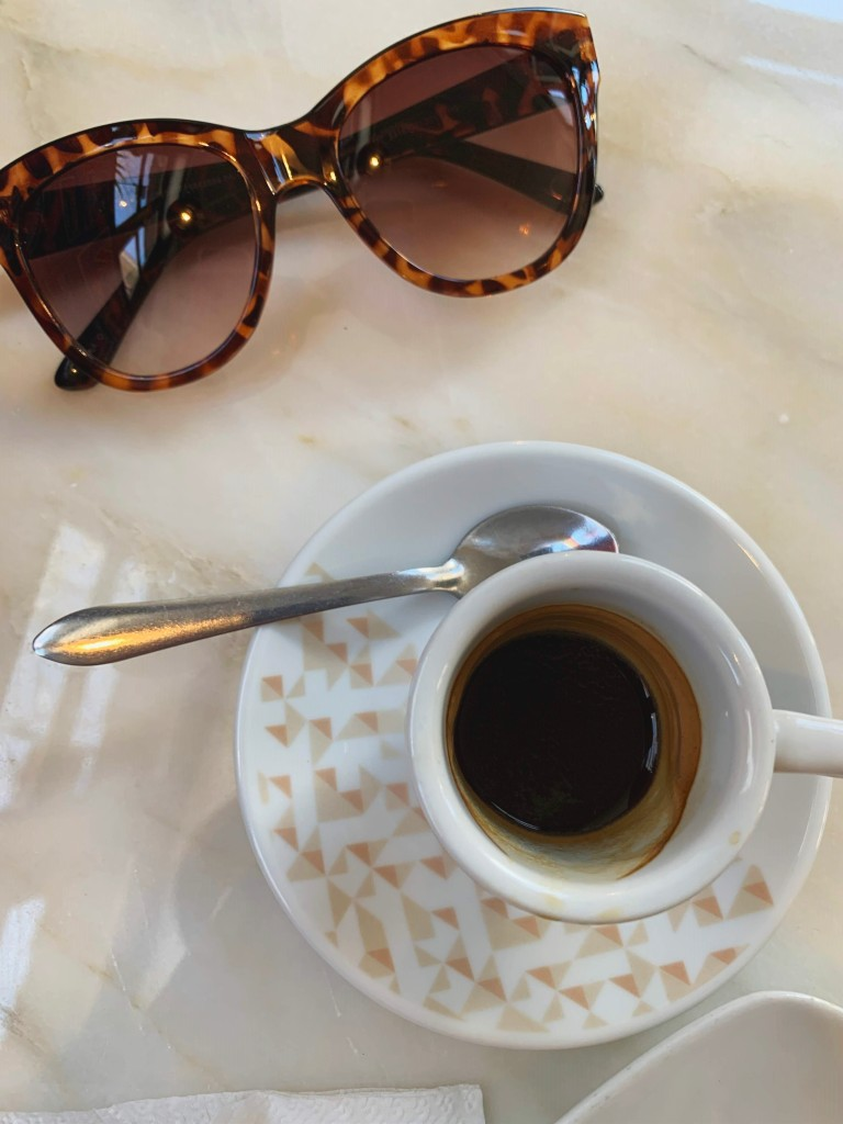 cup of espresso next to sunglasses on a table top
