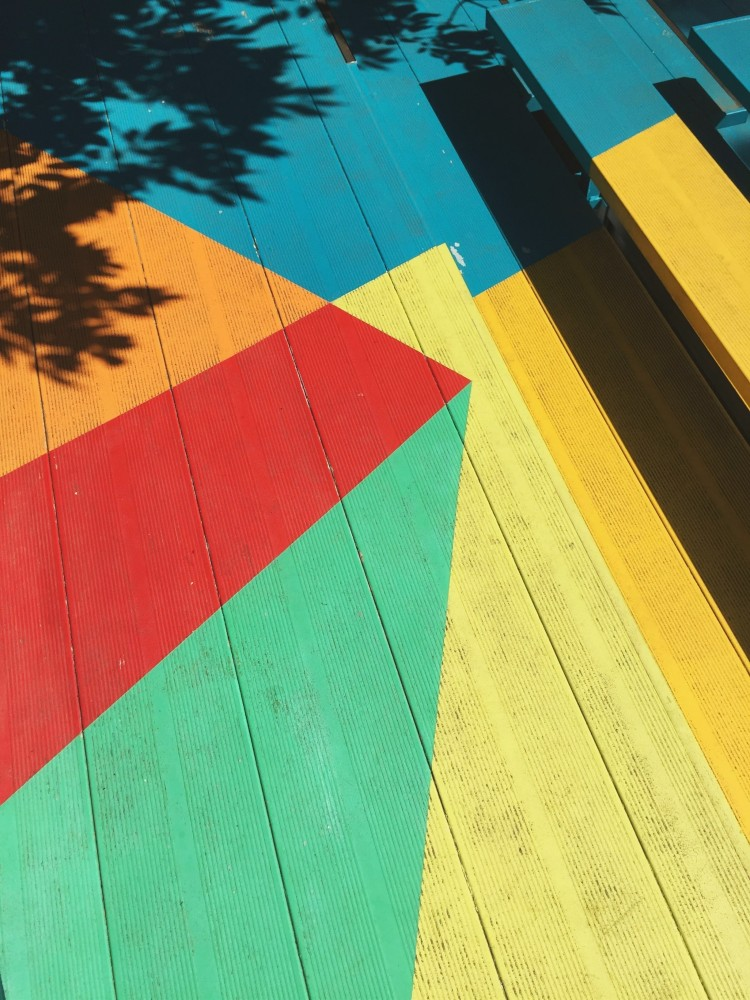 Geometric, rainbow colored design painted onto wood