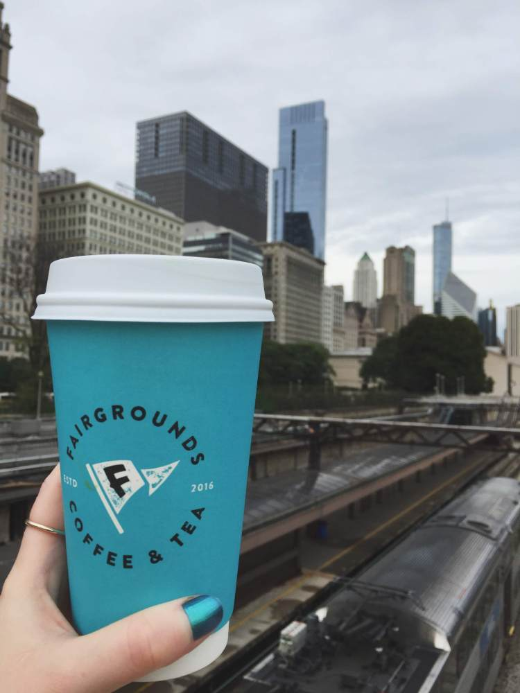 hand holding a coffee cup with city in background