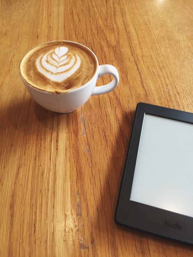 Kindle sitting on a table next to a latte