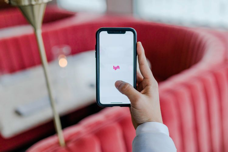 hand holding a smartphone that says Lyft on the screen