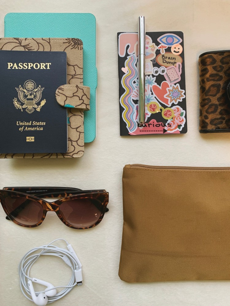 flat lay with notebook, sunglasses, passport, and more