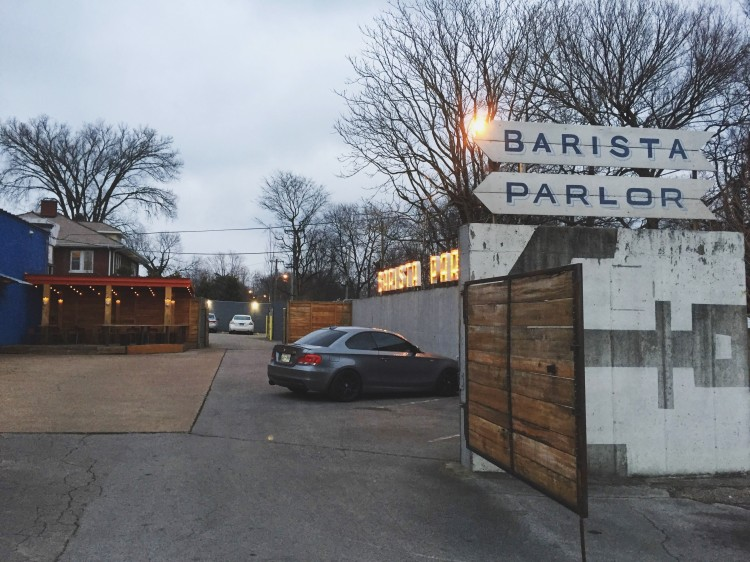 view of parking lot with a sign that reads Barista Parlor