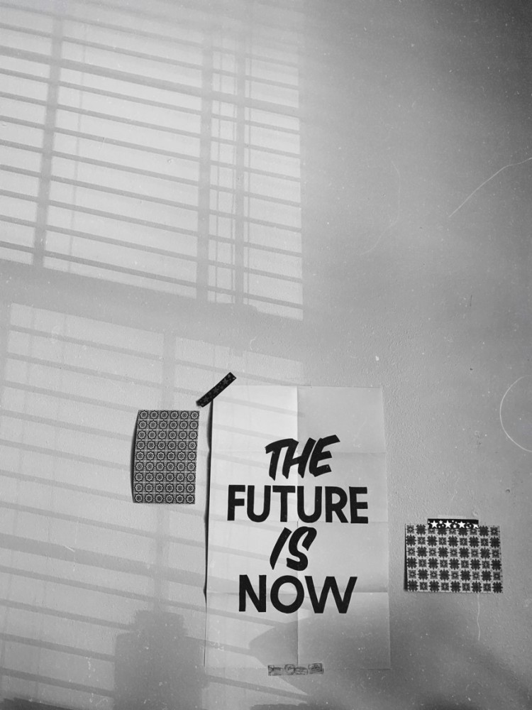 poster taped to a wall that reads the future is now