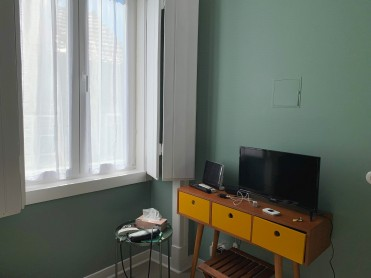 TV on a table, next to a large window